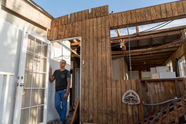 Angel Joel Alvarez Lopez stands by the door of his wood house above his mother's cement house in the Bayamon municipality outside San Juan, Puerto Rico, which was destroyed by Hurricane Maria. He built this wood-and-tin second floor addition about 15 years ago.