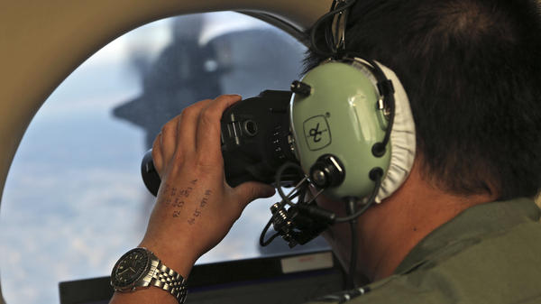 Flight Officer Jack Chen uses binoculars at an observers window on a Royal Australian Air Force P-3 Orion during the search for missing Malaysia Airlines Flight 370 in the southern Indian Ocean in March 2014.