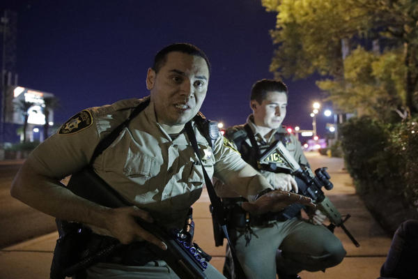 Police officers advise people to take cover near the scene of a shooting near the Mandalay Bay resort and casino on the Las Vegas Strip, Sunday, Oct. 1, 2017, in Las Vegas. (John Locher/AP)