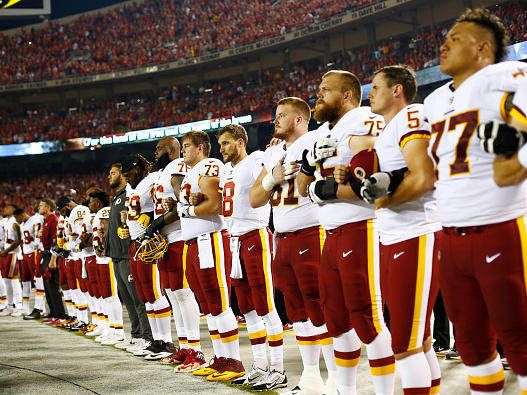 The Washington, D.C., football team stands at attention while linked in arms during the national anthem before Monday night's game against the Kansas City Chiefs at Arrowhead Stadium in Kansas City, Mo.