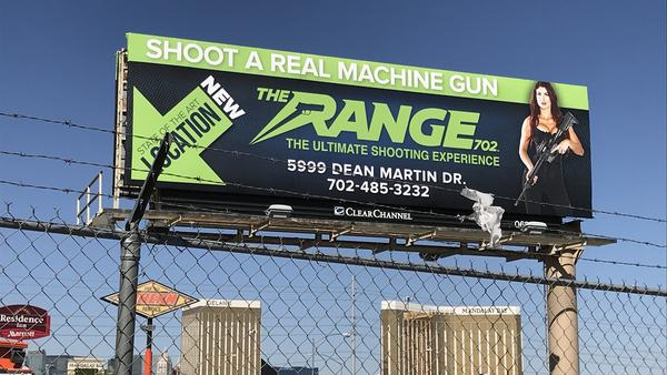 A billboard advertising a gun tourism business in Las Vegas hovers above the Mandalay Bay Hotel, site of a mass shooting Sunday night that killed 58 people and injured nearly 500.