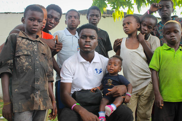 James Okina, founder of the nonprofit Street Priests, poses with street kids in Calabar, Nigeria.