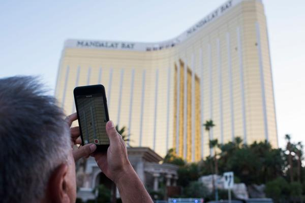 A man on the Las Vegas Strip on Oct. 4, 2017, films on his phone the two broken windows in the Mandalay Bay hotel from which killer Stephen Paddock let loose the worst mass shooting in modern American history on Oct. 1, 2017 at a country music festival across the street in Las Vegas. (Robyn Beck/AFP/Getty Images)