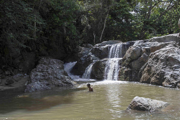 A boy cools down near a waterfall in Loma de Cabrera, Dominican Republic, near the border with Haiti. Local legend has it that Haitians hid in the caves behind the waterfall during the 1937 massacre.