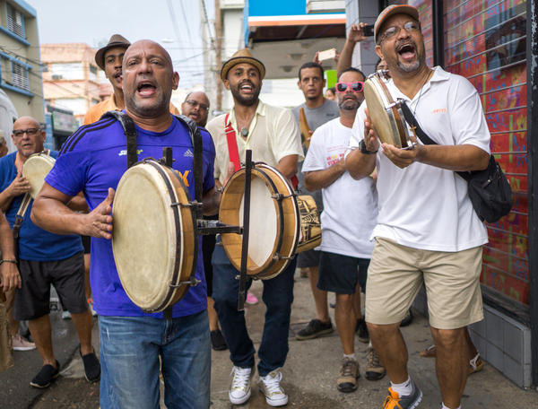 "Hector René ""Tito"" Matos (left), leads a celebratory plena musical bar hopping jam session along the trendy Calle Loiza neighborhood in San Juan, Puerto Rico."