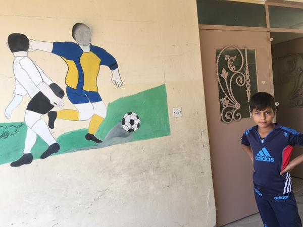 A student in Mosul stands next to a mural defaced by ISIS, whose interpretation of Islam bans the depiction of people or animals. The first school year in three years began in early October but many of the schools are still damaged.