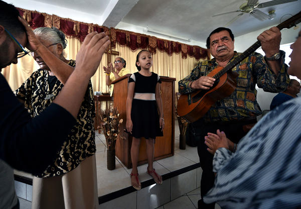 Wilfredo Gonzalez (right), plays guitar during Sunday's service. The church's board president, Gonzalez lost three sisters in a landslide during the hurricane.