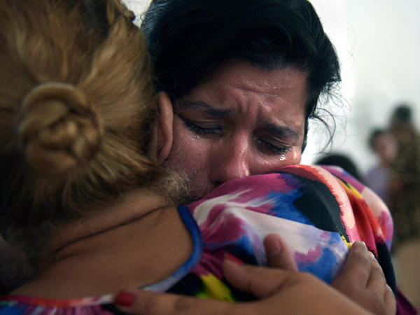 "Ada Reyes weeps and hugs Johanna Nieves Diaz as people comfort one another during the church service. ""I forget about everything going on in the street for a little bit, at least,"" Reyes says."