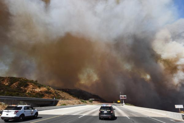A police car blocks the 241 freeway as smoke from the Canyon 2 Fire covers the road near Orange.