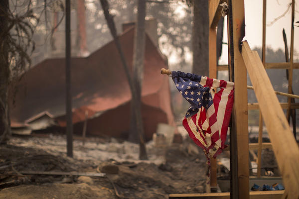 A flag hangs partly melted at a construction site among destroyed houses in Soda Canyon.  Some 170,000 acres were burning Wednesday.