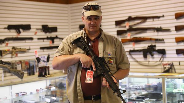 "Shop owner Jeff Binkley displays an AR-15 ""Sport"" rifle at Sarge's Sidearms on Sept. 29, 2016 near Benson, Ariz."