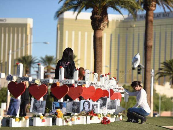 Fifty-eight white crosses for the victims of the shooting on the Las Vegas Strip earlier this month are arrayed Oct. 6 just south of the Mandalay Bay hotel. The shooter fired down on a crowd of concertgoers from a room in the hotel, and on Thursday its parent company disputed the police timeline of the attack.