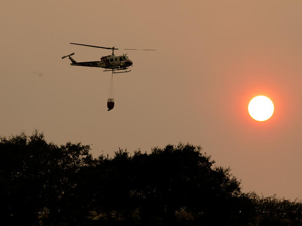 A helicopter flies through the smokey sky to drop a load of water on a wildfire on Thursday in Sonoma, Calif.