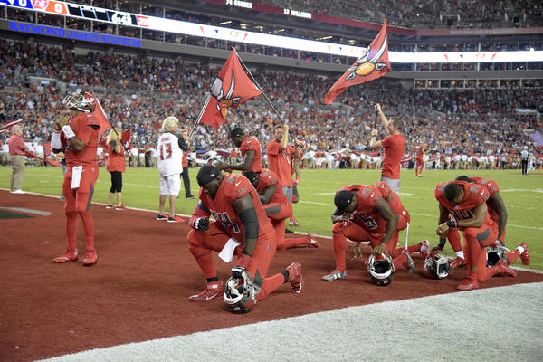 Tampa Bay Buccaneers players kneel in prayer in the end zone before an NFL football game against the New England Patriots Thursday, Oct. 5, 2017, in Tampa, Fla. (Phelan M. Ebenhack/AP)