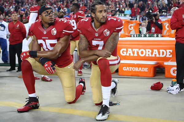 San Francisco 49ers Eric Reid and Colin Kaepernick kneel at a football game in 2016. (Daniel Gluskoter/AP)
