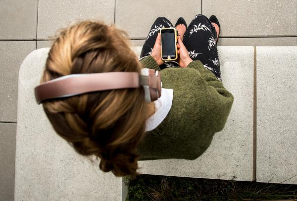 She's not tuning in, she's tuning inward — letting go of stress, or at least trying to, with a mindfulness app on her phone.