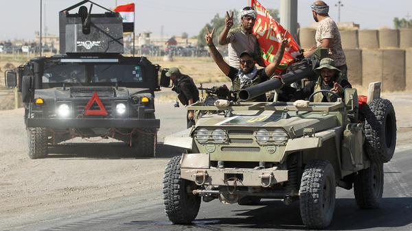 Iraqi forces flash victory signs as they advance toward Kirkuk. Iraqi forces clashed with Kurdish fighters near the disputed city, seizing a key military base and other territory in a major operation sparked by a controversial independence referendum.