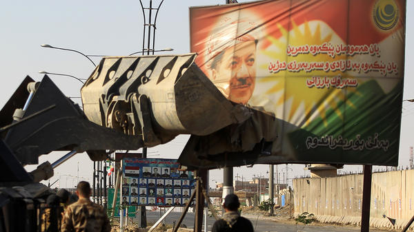 Iraqi forces use heavy equipment to damage a poster of Iraqi Kurdish President Massoud Barzani on the southern outskirts of Kirkuk, as Baghdad seeks to take control of the city from the Kurds.