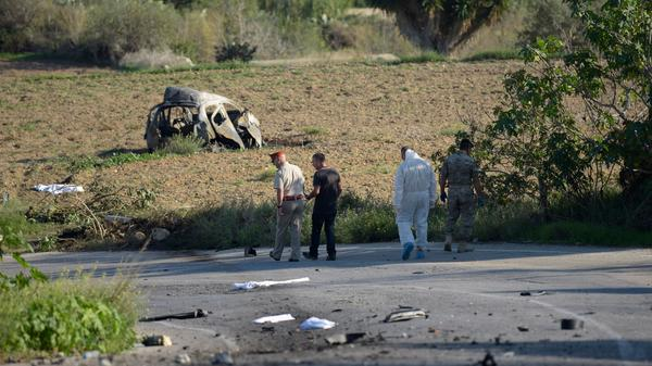 Police and forensic experts inspect the wreckage of a car bomb believed to have killed journalist Daphne Caruana Galizia close to her home in Bidnija, Malta, on Monday. The force of the blast broke her car into several pieces, witnesses said.
