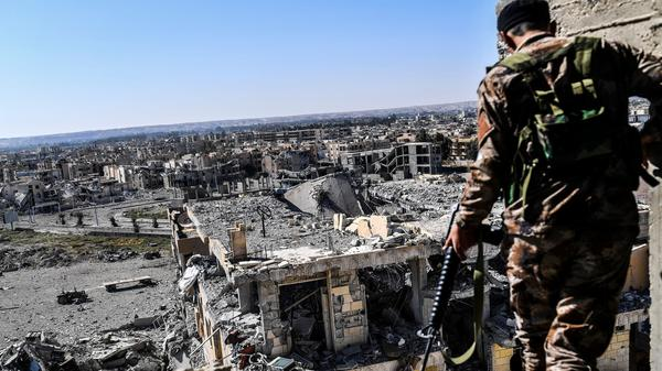 A member of the Syrian Democratic Forces walks on a building near Raqqa's stadium Monday, as they cleared the last positions on the front line in the fight against ISIS.