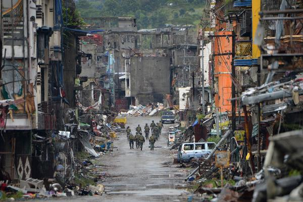 Philippine soldiers walk past destroyed buildings in Marawi's Bangolo district on Tuesday.