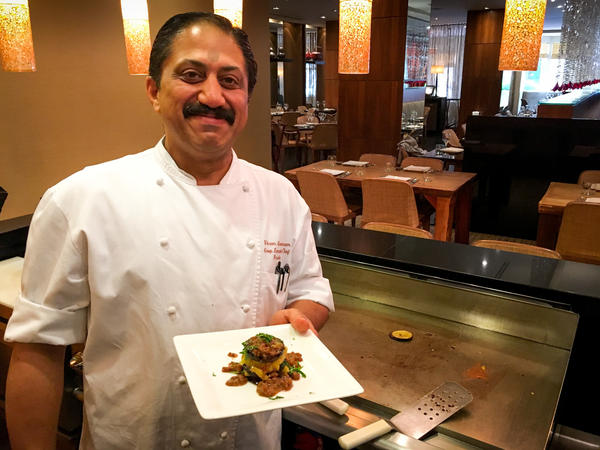 "Rasika chef Vikram Sunderam, here with a towering dish of eggplant and potato, says, ""Indian cuisine is a very personal cuisine. It's made from family to family, how they like to cook."""