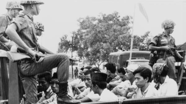 Indonesian soldiers stand guard over members of the youth wing of the Indonesian Communist Party, who were packed into a truck to be taken to a Jakarta prison in October 1965. Over the next few months, the government's military leadership carried out the systematic execution of hundreds of thousands of people.