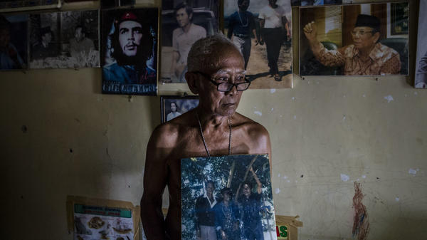 A former prisoner holds a photo of his fellow inmates during his 14-year imprisonment for suspected communist ties.