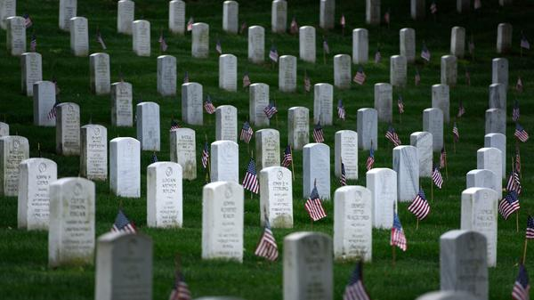 American flags are placed at graves at Arlington National Cemetery in Virginia on May 25, in preparation for Memorial Day.