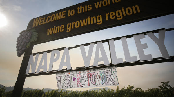 A handmade sign is seen attached to the Napa Valley welcome sign on Oct. 16, 2017 in Oakville, Calif. At least 40 people are confirmed dead, dozens are still missing, and at least 5,700 buildings have been destroyed since wildfires broke out a week ago.