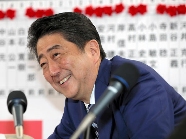 Japanese Prime Minister and ruling party president Shinzo Abe smiles after the general election Sunday in Tokyo in which his ruling party won a clear majority.