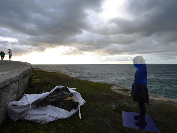 A runner passes a ghostly sculpture on display between Bondi Beach and Tamarama Beach in Sydney.