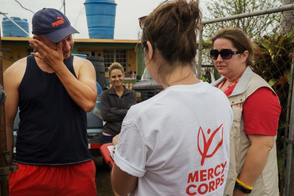 Argenis Ramos, 34, wipes a tear while answering questions for a field research survey by Mercy Corps staffers Alexa Swift (center) and Jill Morehead. Ramos' wife, Karian Batista, looks on.
