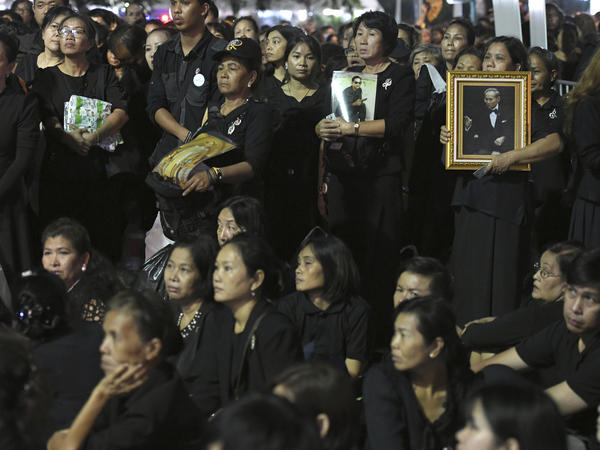 Thai mourners holding portraits of the late King Bhumibol Adulyadej line up to take part in the Royal Cremation ceremony in Bangkok, on Wednesday.