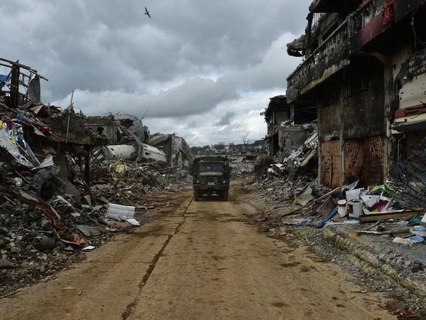 A military vehicle drives past bombed-out buildings in Marawi on the southern Philippine island of Mindanao on Oct. 25, days after the military declared the fighting against ISIS-inspired Muslim militants over.