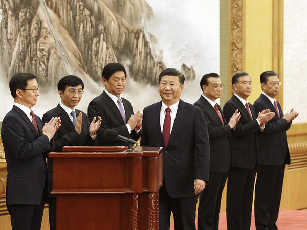 Xi Jinping (center) approaches the podium as other members of the Communist Party's new Politburo Standing Committee applaud on Wednesday. Xi unveiled a new leadership lineup that included no clear potential successors, raising questions about whether he might seek to stay in office beyond 2022.
