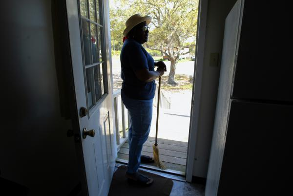 """Cornelia Walker Bailey is pictured in the kitchen doorway of her Wallow Lodge before sweeping the front stoop. Bailey, who died Oct. 15, was considered the Geechee """"griot,"""" a West African term for storyteller, and fought to keep sacred the community's history and way of life, especially its food culture."""