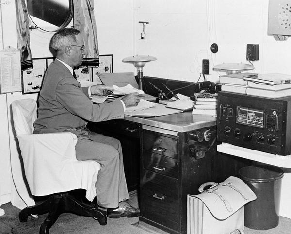 Aboard the cruiser Augusta, President Harry S. Truman, with a radio at hand, reads reports of the first atomic bomb raid on Japan, Aug. 6, 1945, while en route home from the Potsdam conference, where the Japanese flatly rejected the Potsdam Declaration. (AP Photo)