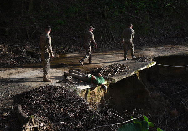 Timothy Bird (second from left), a volunteer with the nonprofit Crisis Relief Team, peers over a washed-out road to determine whether it is safe for the troops' Jeeps to pass.