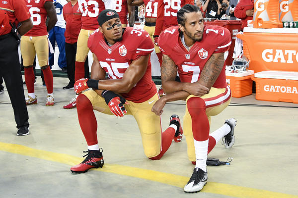 Colin Kaepernick, right, and Eric Reid of the San Francisco 49ers kneel in protest during the national anthem prior to playing the Los Angeles Rams in their NFL game on September 12, 2016.
