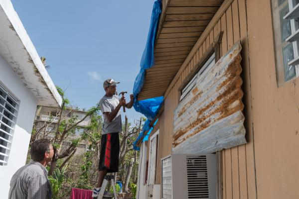 Handyman Edgar Santiago nails a blue tarp on the roof of a destroyed home. Legal volunteers tell residents to clean up the debris and damage as best as they can, take photos, get it repaired and hold onto the receipts.