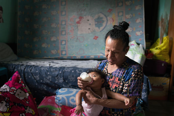 Ma Ona, a waria who has HIV, holds Nira, a baby who lost her mother to complications from AIDS. Ona wants to adopt her.
