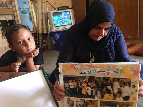 Mustafa's mother Nidhal Aswad looks at a photo album from Mustafa's time in Portland. Mustafa's younger brother Abdul Rahman looks on.