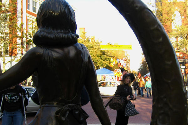 "A woman dressed as a witch is framed by a statue in downtown Salem of Samantha Stevens, the witch on the TV show ""Bewitched."""