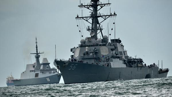 The USS John S. McCain sails toward a naval base in Singapore in August, the massive dent in its side visible on the right side of the frame. The destroyer had collided with a tanker just hours before — the second such deadly collision involving a U.S. Navy warship in several months.