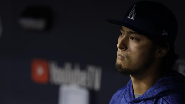 Los Angeles Dodgers starting pitcher Yu Darvish watches from the dugout during the eighth inning after being pulled for a reliever early in the game.