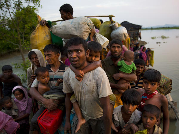 Rohingya Muslims carry their young children and belongings after crossing the border from Myanmar into Bangladesh, near Palong Khali, Bangladesh, on Wednesday.