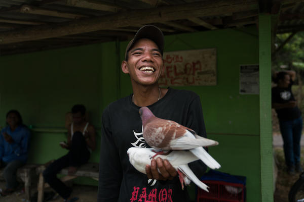 "Sumarjan is bursting with excitement after his one-year-old pigeon Panjol wins the day's race, earning him about $9. ""This is my first time winning the competition,"" he says. ""I'm so happy. This is only a small competition. I can't imagine winning a bigger competition."""