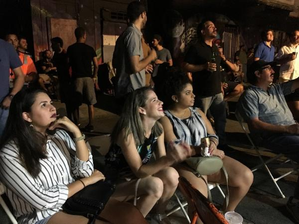Tahiri Berrios, Camille Axtmayer and Liz Cruz watch the final game of the World Series in the street outside Esquina Watusi, a bar in central San Juan.