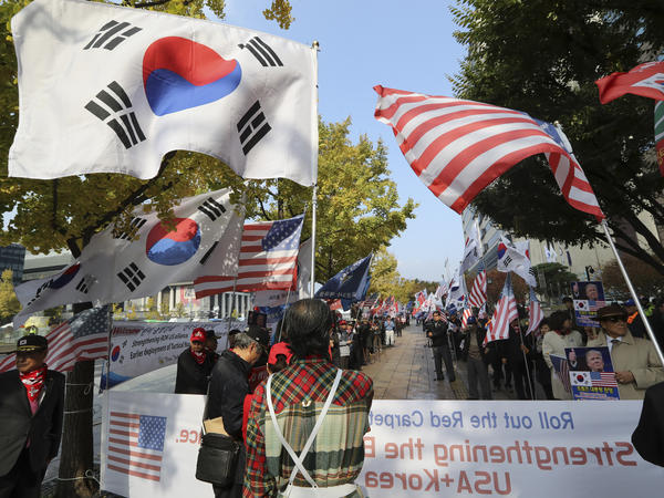 South Koreans hold flags during a rally welcoming U.S. President Donald Trump's visit to the country in downtown Seoul, South Korea, on Friday.